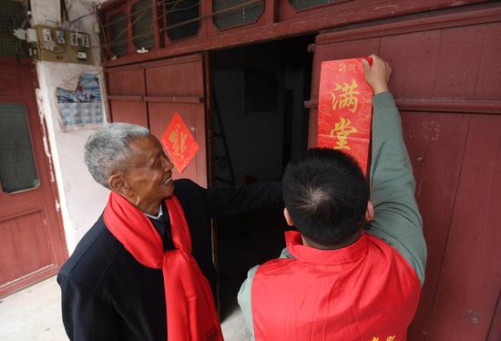 志愿者为留守老人张贴对联。  王刚 摄