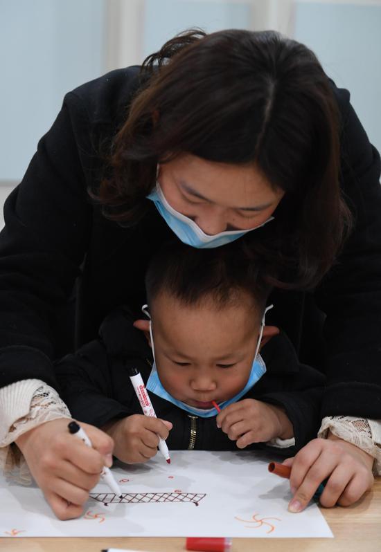 一位家长陪孩子完成新年主题绘画。  王刚 摄