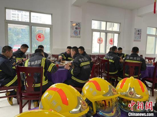 图为消防员穿着救援服用餐。袁超 摄