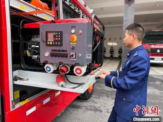 图为消防员唐洪旭向记者展示救援器材。袁超 摄