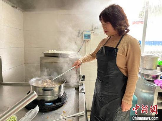 图为沈大涵的妈妈彭媛在队里的厨房为队员做菜。袁超 摄