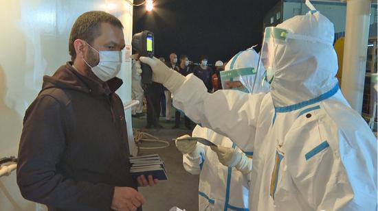 臺州海關駐玉環辦事處關員對船員測量體溫。林俐 攝