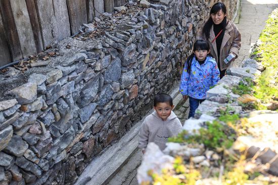 图为游客在体验仡佬古寨石巷。瞿宏伦 摄