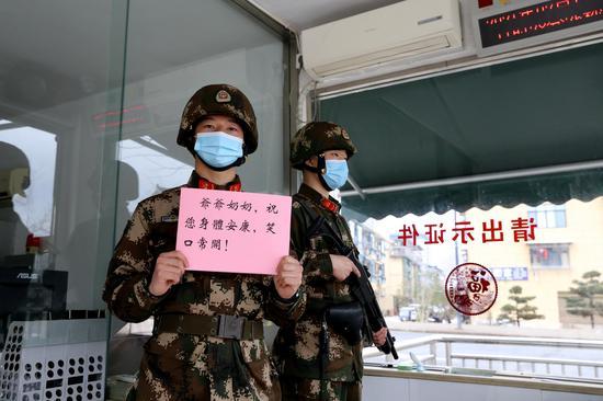 """武警丽水支队战士李瑞(左1)在哨位上展示写给远方亲人的""""一句话""""。刘治乾 摄"""