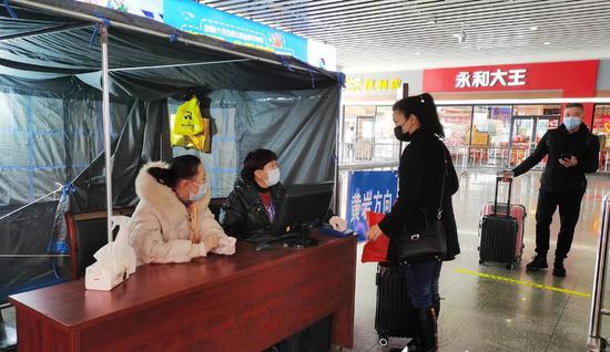 台州火车站防疫人员对旅客身份证进行核验。解文雅 摄