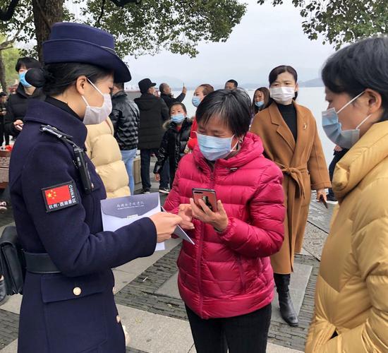 """图为:西湖女子巡逻队为游客免费发放""""防疫福袋""""。王潇婧 摄"""