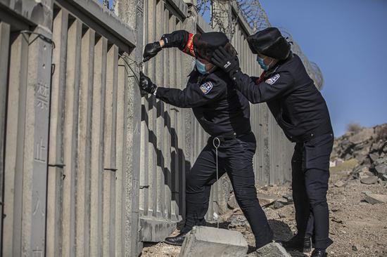 大风中民警对高铁线路松动护栏进行捆绑  。