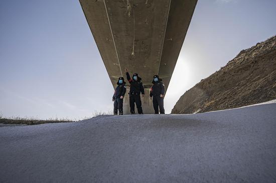 民警在大风中利用制高点对兰新高铁乌拉泊区段线路进行安全巡查。