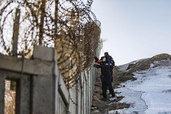 民警对兰新高铁乌拉泊区段高铁线路护栏进行检查   。