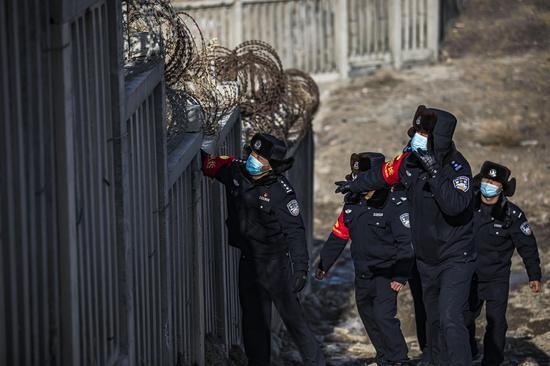 民警对大风刮到高铁护栏上的杂物进行清理 。