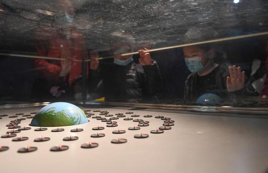 一位小朋友在观看地球模型。王刚 摄