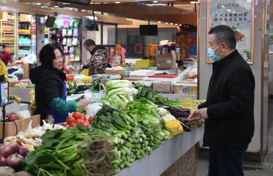 一位市民在农贸市场内买菜。王刚 摄