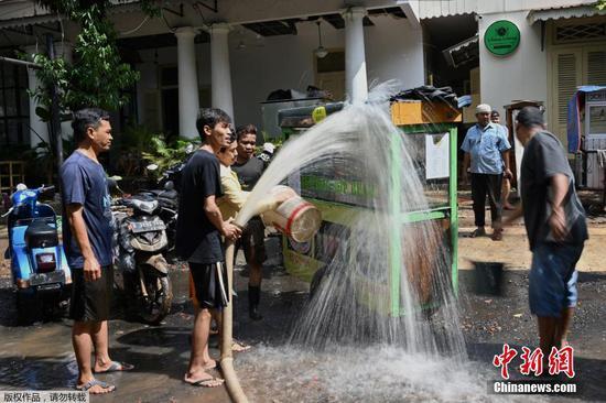 当地时间2月21日,印度尼西亚首都雅加达,洪水退去后,街头小贩冲洗自家摊位上的泥浆。