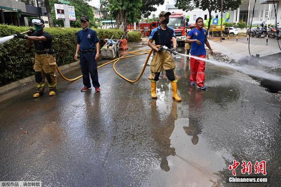 当地时间2月21日,印度尼西亚首都雅加达,洪水退去后,消防队员进行清淤工作,冲洗道路上的泥浆。此前,印度尼西亚部分地区因季节性的暴雨而遭到洪水侵袭。