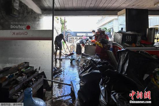 当地时间2月21日,印度尼西亚首都雅加达,洪水退去后,店铺员工在店内清扫。