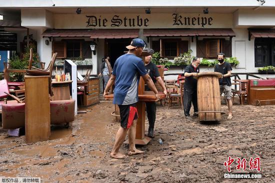 当地时间2月21日,印度尼西亚首都雅加达,洪水退去后,人们将餐厅里被洪水浸泡过的家具放在外面晾干。