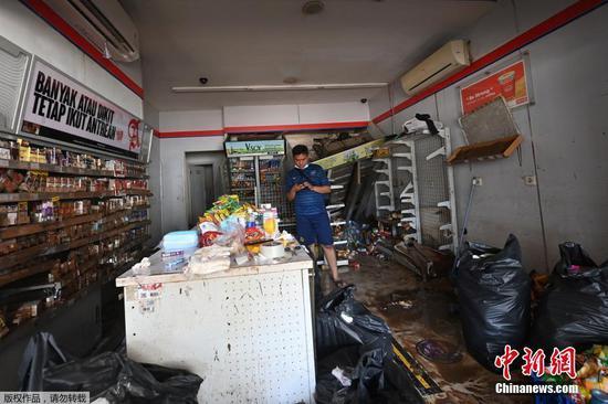 当地时间2月21日,印度尼西亚首都雅加达,洪水退去后,路人从被洪水冲毁的建筑前走过。