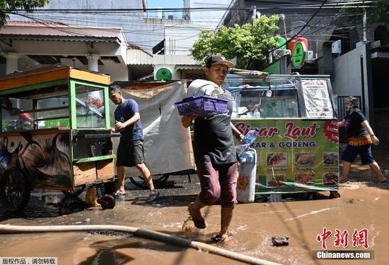 地时间2月21日,印度尼西亚首都雅加达,洪水退去后,街头小贩清理食品摊位上的泥浆。