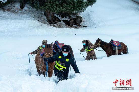 新疆民警携护边员齐腰深积雪中巡边