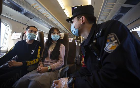D2708次列车乘警达尼亚尔·迪力木拉提向返校学生进行反电信诈骗提示。