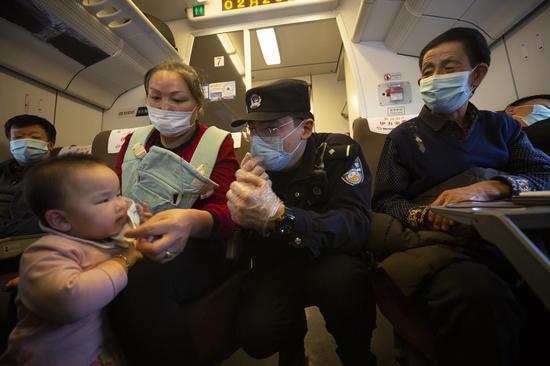 """D2708次列车乘警达尼亚尔·迪力木拉提叮嘱""""小旅客""""注意佩戴好口罩。"""