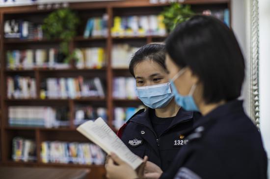 青年民警党员在《警察书屋》认真阅读有关党史类的书籍。