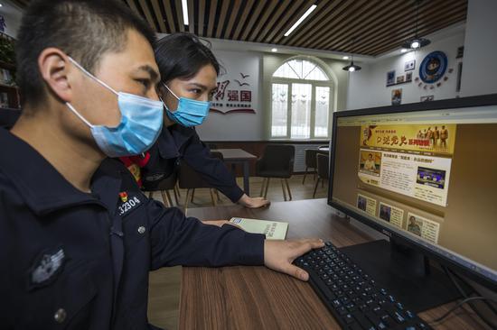 青年党员民警利用网络查找有关党史内容的电子书刊。