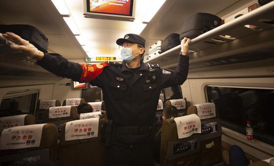 D2708次列车乘警达尼亚尔·迪力木拉提在车厢叮嘱旅客行李架上形状相近的背包勿拿错。