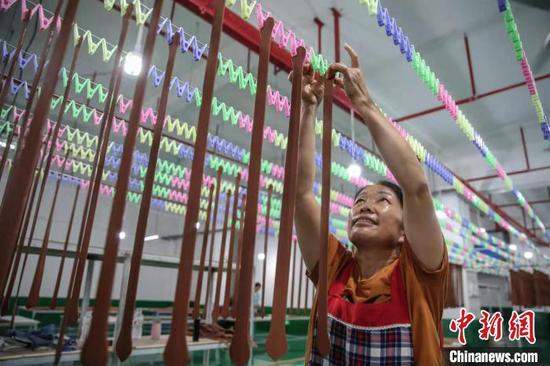 资料图:搬迁户在重庆华龙棋牌下载望谟易地扶贫搬迁点扶贫工厂工作。 瞿宏伦 摄