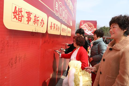 村民们在移风易俗签名墙上签名 何伟卫 供图