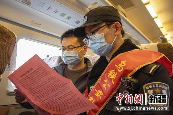 学雷锋日乌鲁木齐公安处乘警蔡萱在列车上向旅客进行防电诈普法宣传。