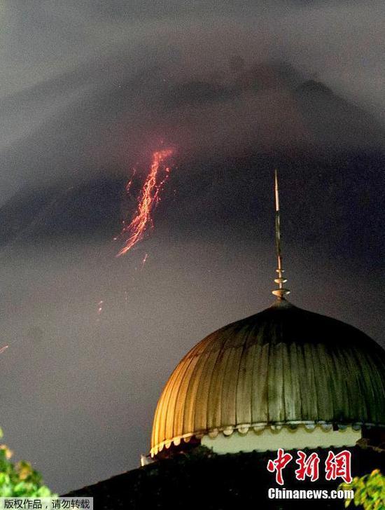 當地時間3月7日,印度尼西亞默拉皮火山噴發,滾滾巖漿順著山體流淌。圖為從遠處建筑眺望火山。