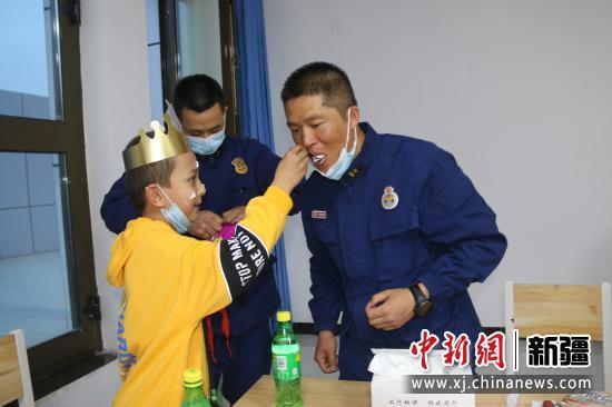 图为比拉力·阿迪力给消防员叔叔分享生日蛋糕。