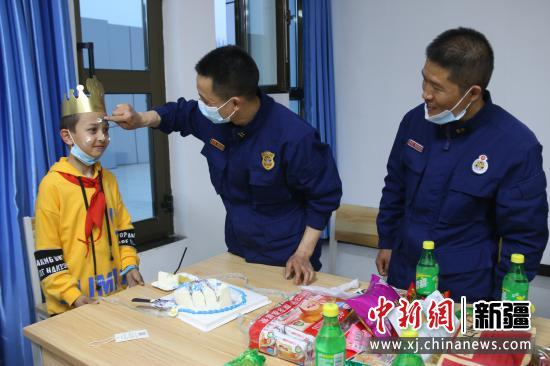图为消防员给比拉力·阿迪力抹生日蛋糕。