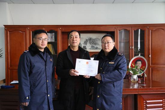 绍兴市市场监管局工作人员为企业颁发《化妆品生产许可证》。  俞丹 摄