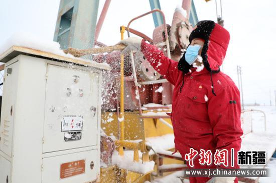 新疆油田采油二厂员工正在清理突如其来的暴雪。  王涛 摄
