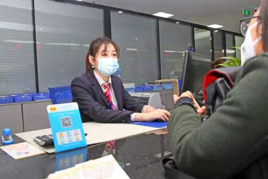 金华医保中心工作人员为市民办理医保业务。  黄鸣 摄