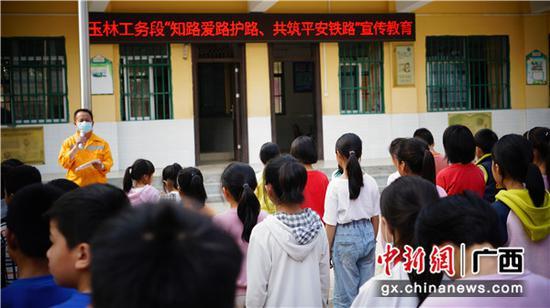 玉林工務段路外安全宣傳小分隊隊員在給學校師生講解宣講電氣化鐵路安全法規、規定和九個嚴禁、十四個不得的安全知識。譚育俊 攝