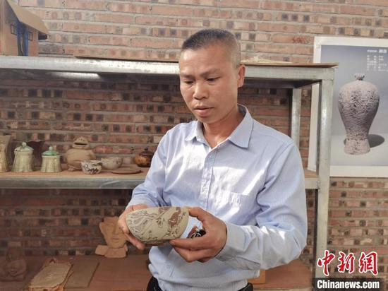 洪江村村民韦伟毅展示自己制作的陶艺。 周燕玲 摄