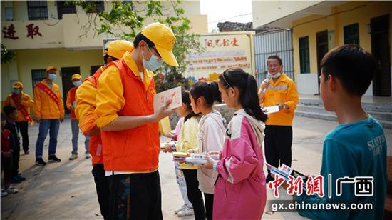 玉林工務段路外安全宣傳小分隊隊員在給學校小學生發放《廣西壯族自治區鐵路安全管理條例》宣傳小冊子、宣傳單和小學生的學習文具等物品。譚育俊 攝
