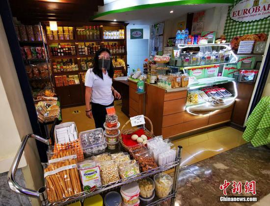 當地時間3月28日,菲律賓首都馬尼拉CBD馬卡蒂綠帶商圈,小食品商販在防護后照常營業。 中新社記者 關向東 攝