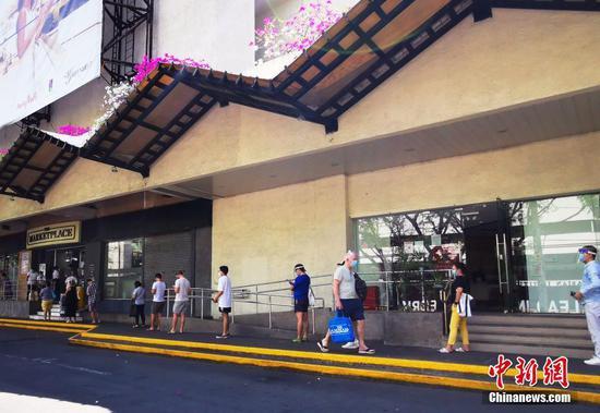 當地時間3月28日,菲律賓首都馬尼拉CBD馬卡蒂綠帶商圈,市民在超市外排隊等候進入采購生活物資。 中新社記者 關向東 攝
