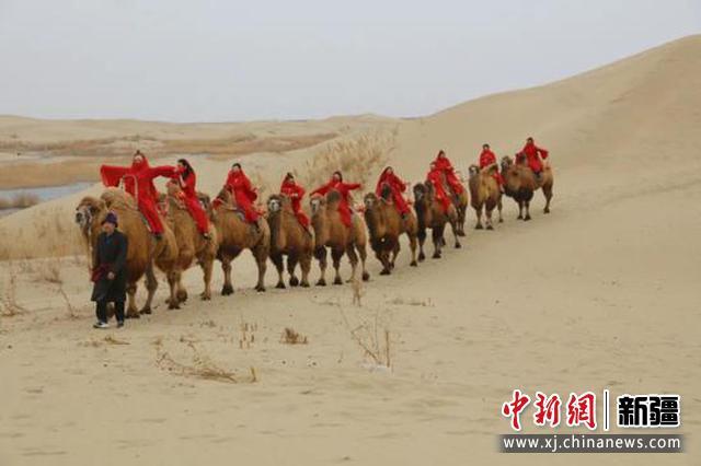在尉犁县罗布人村寨景区沙漠里,身着红衣长裙的美丽姑娘们缓行沙坡、骑骆驼。