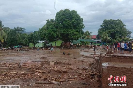 当地时间4月4日,印尼东部弗洛雷斯岛,村民检查遭遇山洪冲击后的村庄损坏程度。
