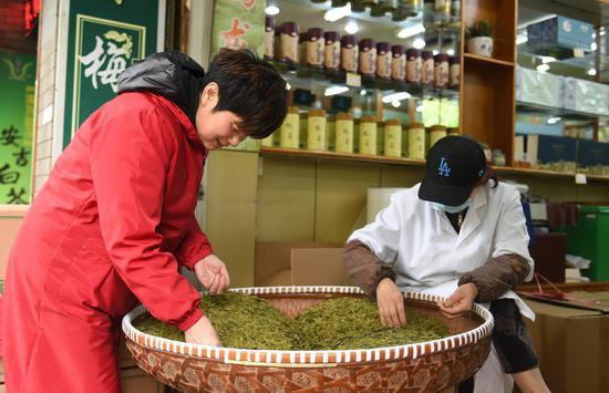 茶叶店工作人员↑在筛选龙井茶叶。  王刚 摄