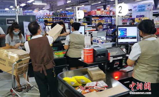 当地时间4月7日,马尼拉CBD马卡蒂绿带商圈一生活超市,市民和售货员戴着口罩和防护面罩购物和收银。马尼拉市进入第二周加强版社区隔离,政府保障市场供应,物价平稳。 中新社记者 关向东 摄