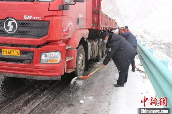 民警利用煤粒等物资对结冰路面化冰,随后对滞留车辆进行分流疏导。 王振 摄
