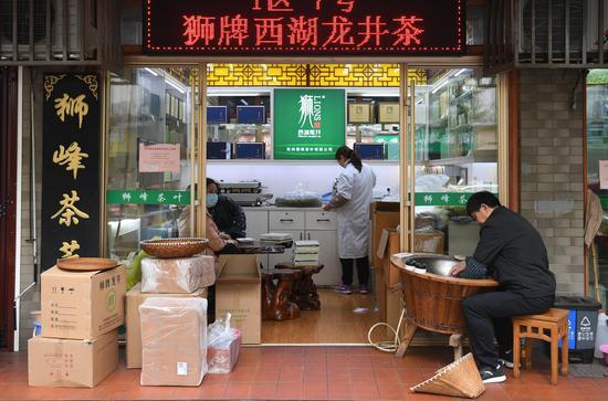 一家龙井茶商铺工作人员忙于炒制、包装龙井◇茶。  王刚 摄