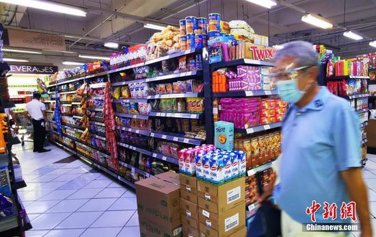 当地时间4月7日,马尼拉CBD马卡蒂绿带商圈一生活超市,市民戴着口罩和防护面罩购物,商场副食品充足。马尼拉市进入第二周加强版社区隔离,政府保障市场供应,物价平稳。 中新社记者 关向东 摄