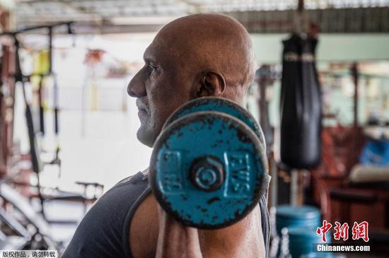 4月8日讯,当地时间3月18日,马来西亚霹雳州,健美运动员A. Arokiasamy正在自己的健身房训练。尽管Arokiasamy年事已高,但曾经是举重冠军的他依然每天在健身房撸铁,他相信保持健康,坚持健康的作息,是抵御新冠病毒的最好办法。